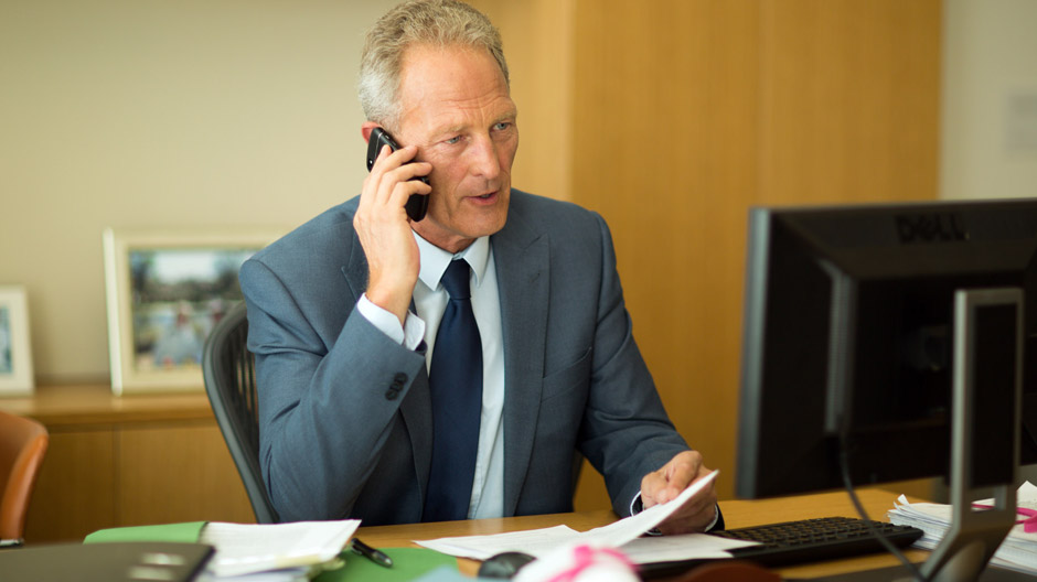 A photograph of a male lawyer on the phone in an office